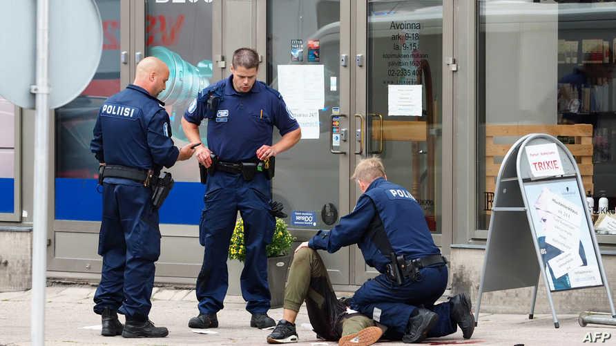 عناصر من الشرطة الفنلندية تتعامل مع المشتبه به في تنفيذ عملية الطعن في توركو بعد إطلاق النار على ساقه