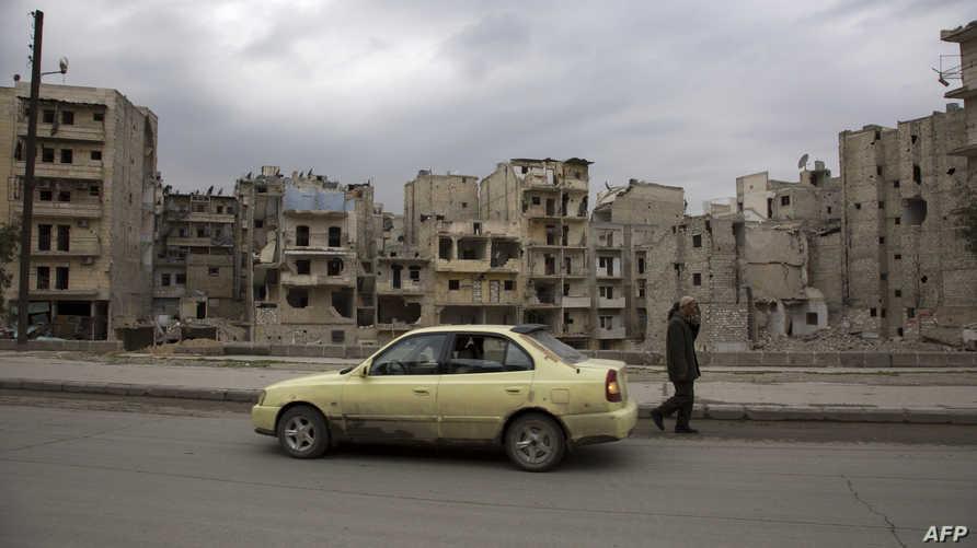 رجل بجانب سيارة أجرة في أحد أحياء مدينة حلب في الثالث من آذار/مارس