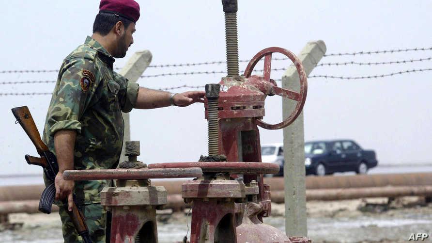 جندي عراقي يحرس أنبوب نفط في العراق- أرشيف