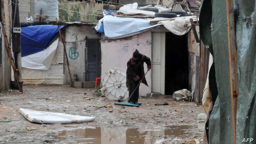 لاجئ سوري يبعد  المياه عن مكان اقامته في أحد مخيمات اللجوء في لبنان