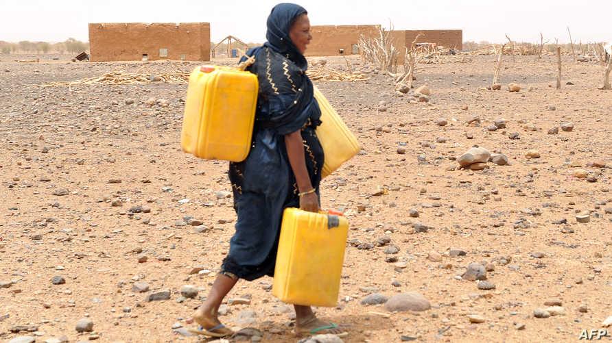 سيدة موريتانية تحمل المياه في أوعية بلاستيكية (أرشيف)