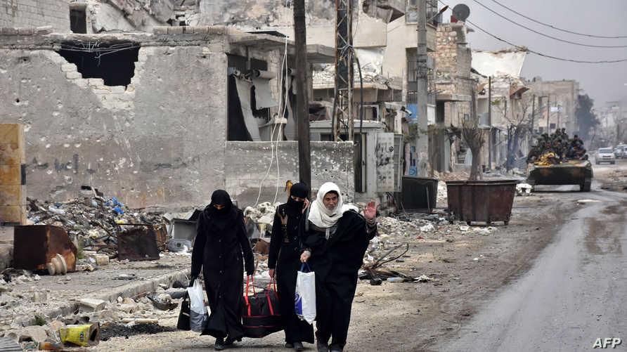 مدنيون خلال مغادرتهم إحدى المناطق شرقي حلب إثر دخول القوات النظامية إليها