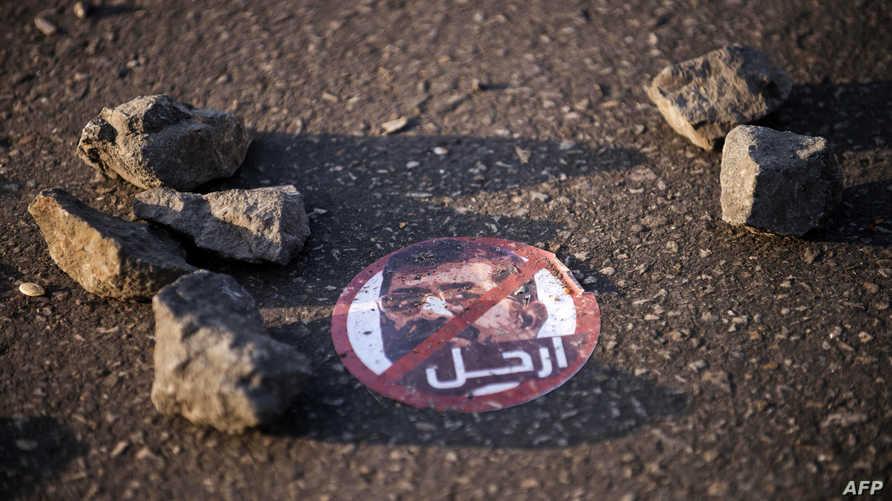 صورة مرسي كتب عليها ارحل على الأرض في منطقة قريبة من القصر الرئاسي في القاهرة