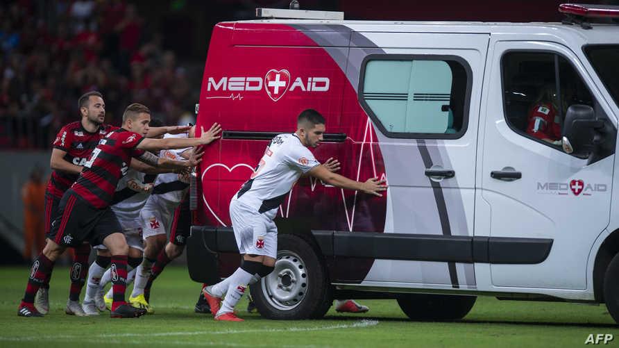 لاعبون يقومون بدفع سيارة الإسعاف التي تعطلت في الملعب