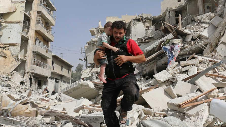 سوري يحمل طفلا بعد أن أخرجه من تحت أنقاض إحدى البنايات إثر غارة في حلب
