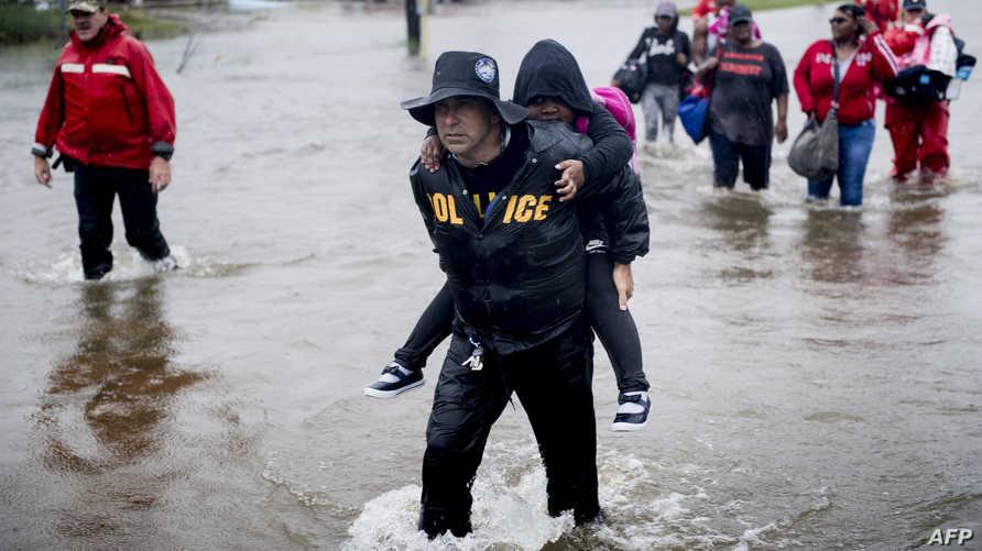 مواطنون وشرطي يحمل طفلا في إحدى المناطق الغارقة بهيوستن