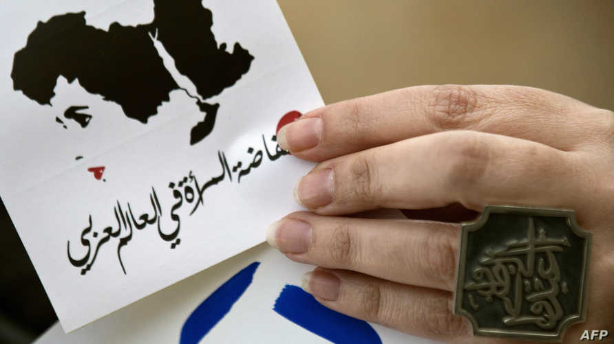 """سيدة ترفع شعار """"انتفاضة المرأة في العالم العربي"""" رفضا للعنف الجنسي ضد النساء في مصر عام 2013"""
