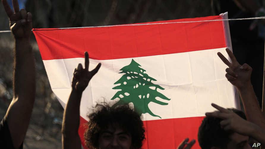 متظاهرون يرفعون علم لبنان.