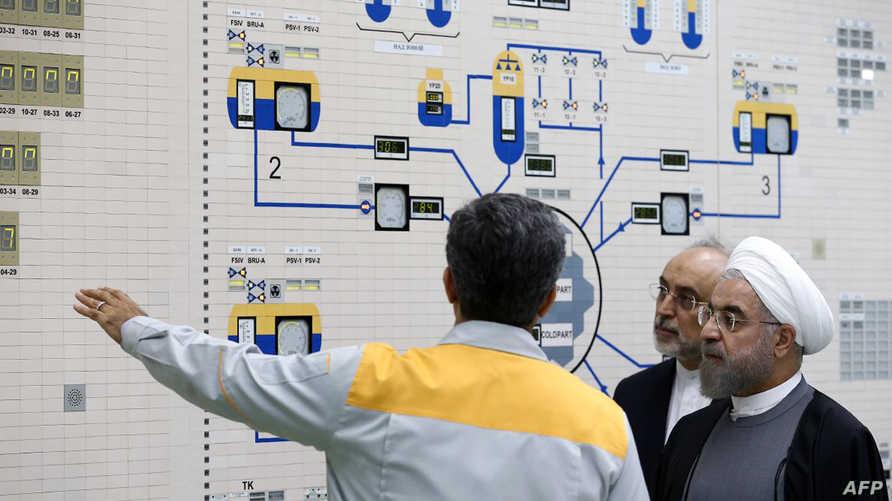 روحاني وصالحي يستمعان لشرح من أحد التقنيين في مفاعل بوشهر النووي (أرشيف)
