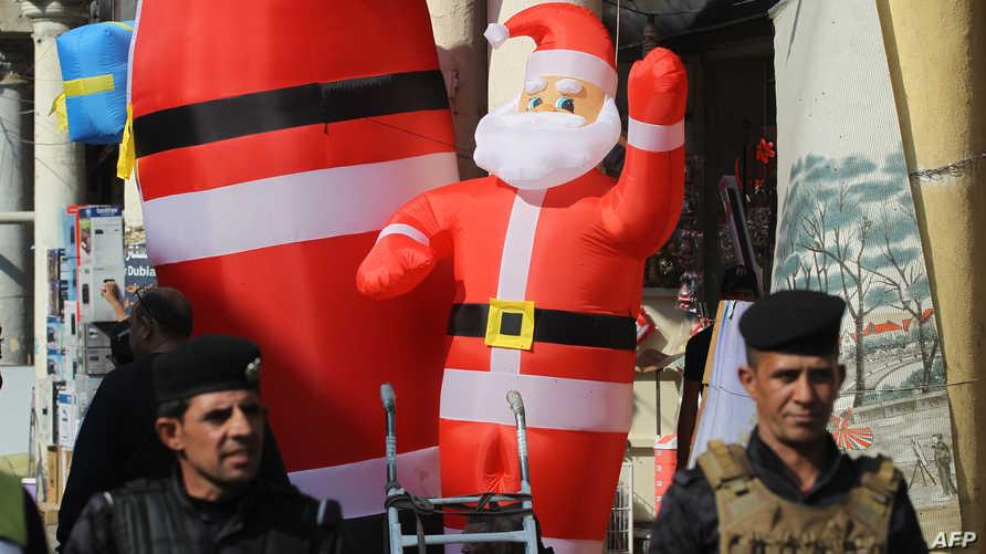 عنصران في الأمن العراقي يقفان أمام محل يبيع هدايا أعياد الميلاد في شارع الرشيد وسط بغداد