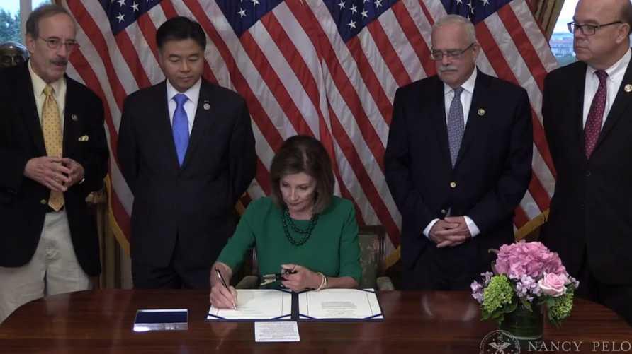 رئيسة مجلس النواب الأميركي نانسي بيلوسي توقع مشروع القرار