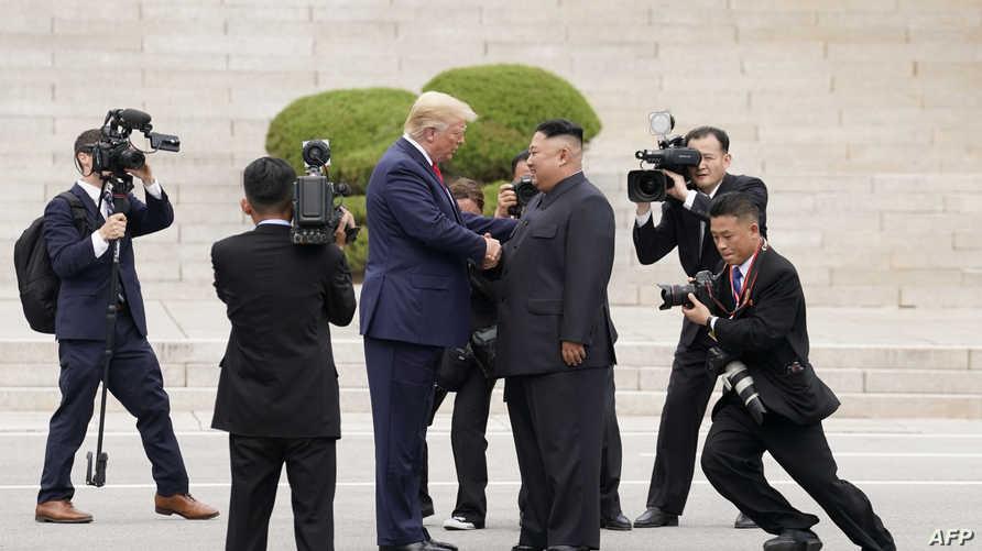 الرئيس الأميركي دونالد ترامب يصافح الزعيم الكوري الشمالي كيم جونغ أونغ