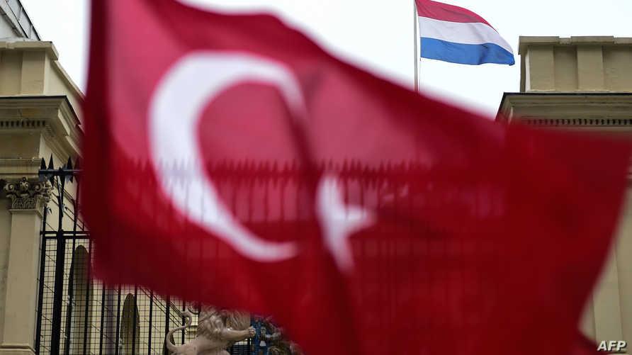 علم تركي يحمله متظاهرون أمام مبنى القنصلية الهولندية في إسطنبول
