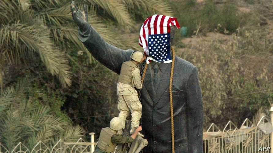جندي أميركي يضع علم الولايات المتحدة على تمثال صدتم حسين في ساحة الفردوس ببغداد - أرشيف