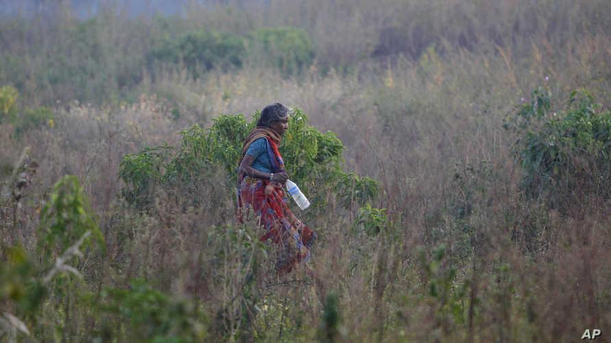 امرأة هندية تغادر حقل يقضي فيه الناس حاجتهم