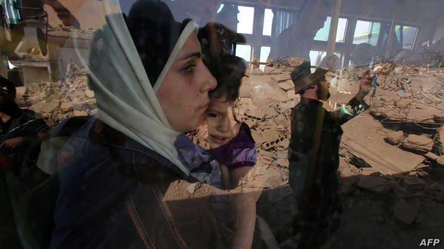 سيدة من داريا تحضن طفلها في الحافلة التي تقلهم خارج المدينة، وتظهر في زجاج النافذة مشاهد الدمار من حولهم.