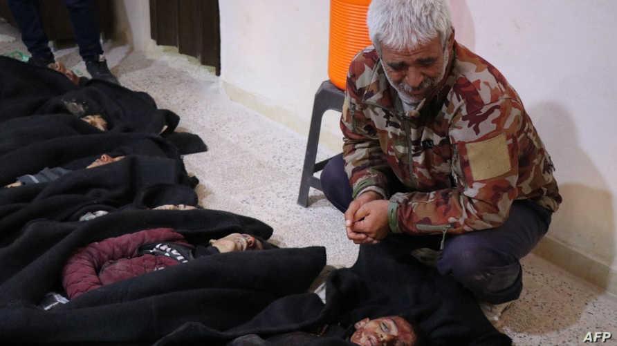 رجل كردي يقف بجانب الأطفال من ضحايا المجزرة التركية في تل رفعت