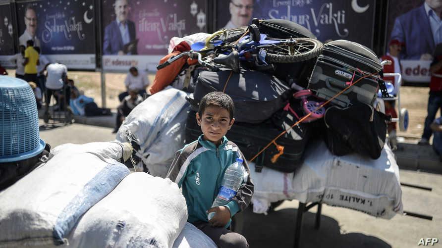 طفل سوري ينتظر عند معبر تركي في طريق عودته إلى مدينة تل أبيض السورية الحدودية