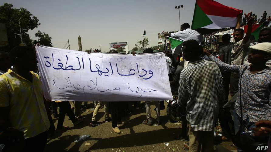 """متظاهر سوداني يرفع لافتة تقول: """"وداعا أيها الطغاة"""""""