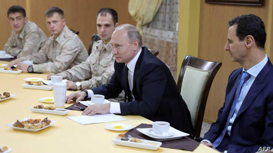 الرئيس الروسي فلاديمير بوتين في اجتماع مع قادة عسكريين روس بقاعدة حميميم قرب اللاذقية بحضور الرئيس السوري بشار الأسد