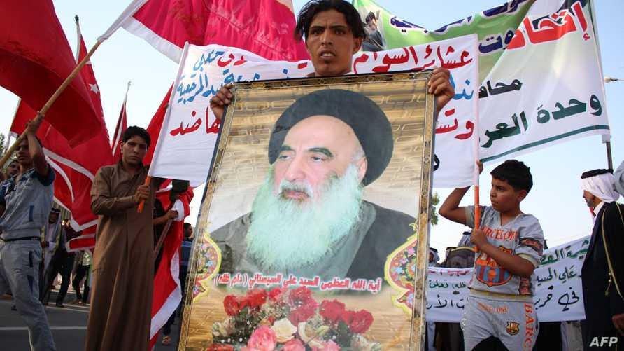 مواطن عراقي يحمل صورة آية الله الكبرى علي السيستاني