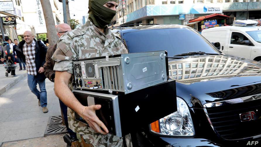 عنصر من الأمن اللبناني يحمل كمبيوتر لمؤسسة مالية في إطار التحقيق حول تحويل أموال لداعش