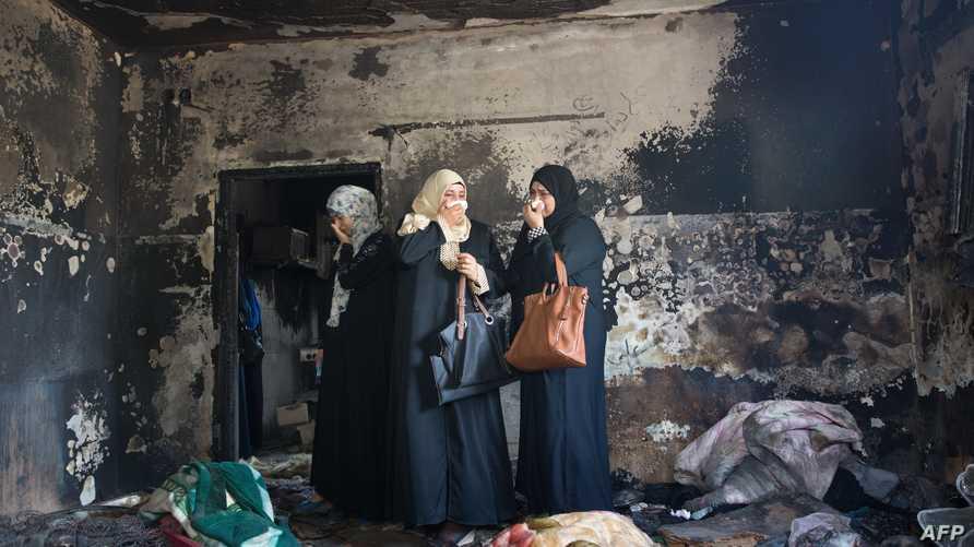 فلسطينيات يتفقدن منزل عائلة دوابشة