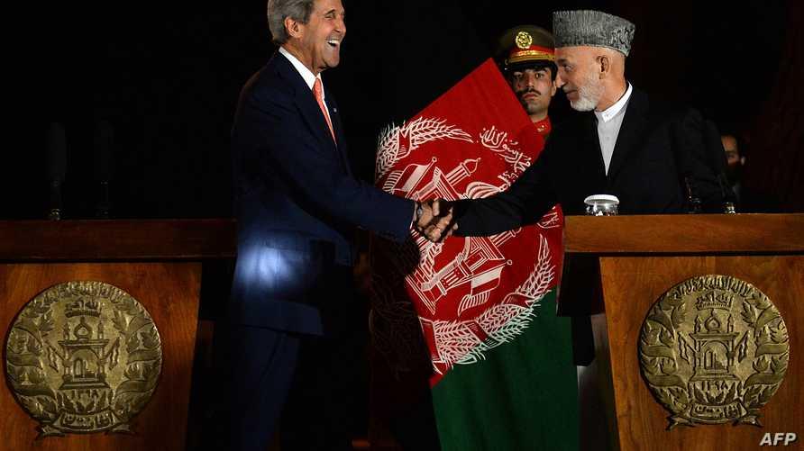الرئيس الأفغاني حامد كرزاي يصافح وزير الخارجية الأميركي جون كيري خلال مؤتمر صحافي في كابول مساء السبت 12 أكتوبر/تشرين الأول 2013