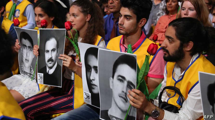 إيرانيون في باريس، يحملون صور أقاربهم الذين قتلهم النظام الحاكم