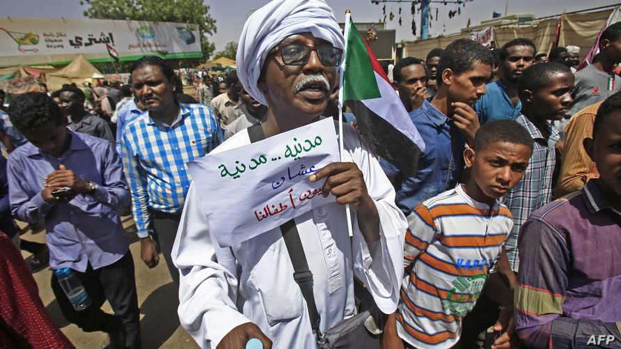 """متظاهر سوادني يرفع شعار: """"مدنية... مدنية عشان عيون أطفالنا"""""""