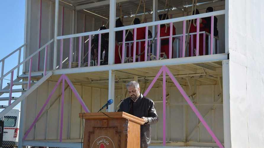 وزير العدل العراقي يلقي كلمة ويظهر في الخلفية تنفيذ حكم الإعدام بعدد من المدانين