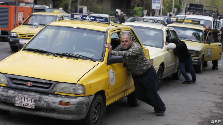 يدفع سيارته في دمشق في انتظار دوره لشراء الوقود