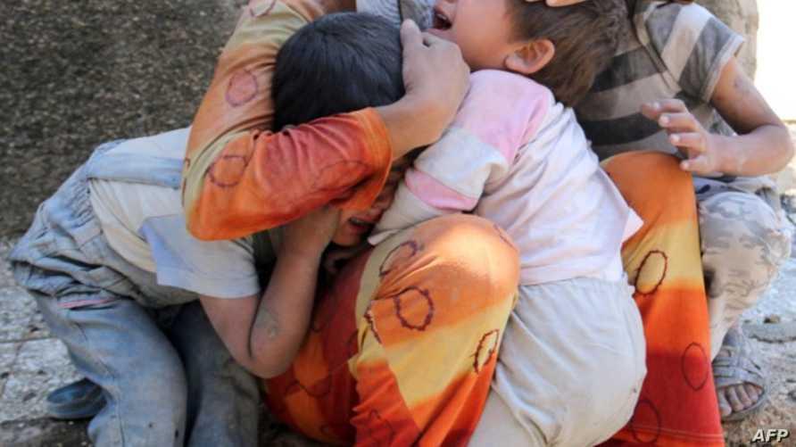 امرأة سورية تحتضن أبناءها/وكالة الصحافة الفرنسية