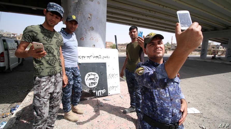 أعضاء في القوات العراقية يلتقطون صورا مع شعار داعش بعد إنزاله في إحدى مناطق الفلوجة