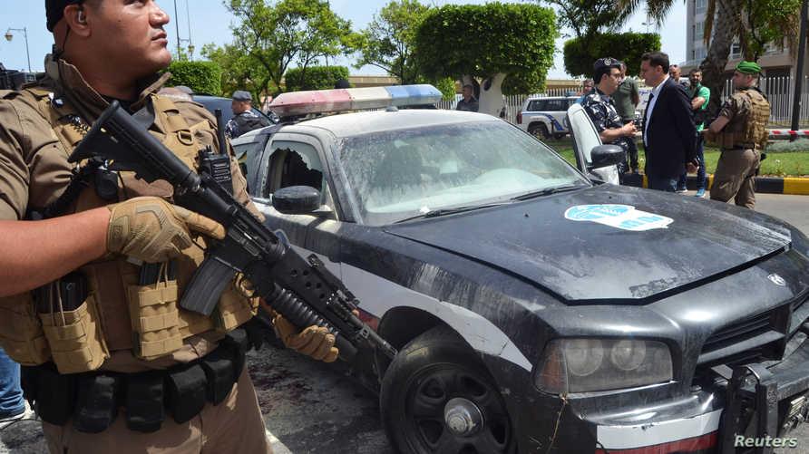 رجل أمن لبناني بالقرب من سيارة الشرطة التي تعرضت لهجوم إرهابي في طرابلس شمالي لبنان