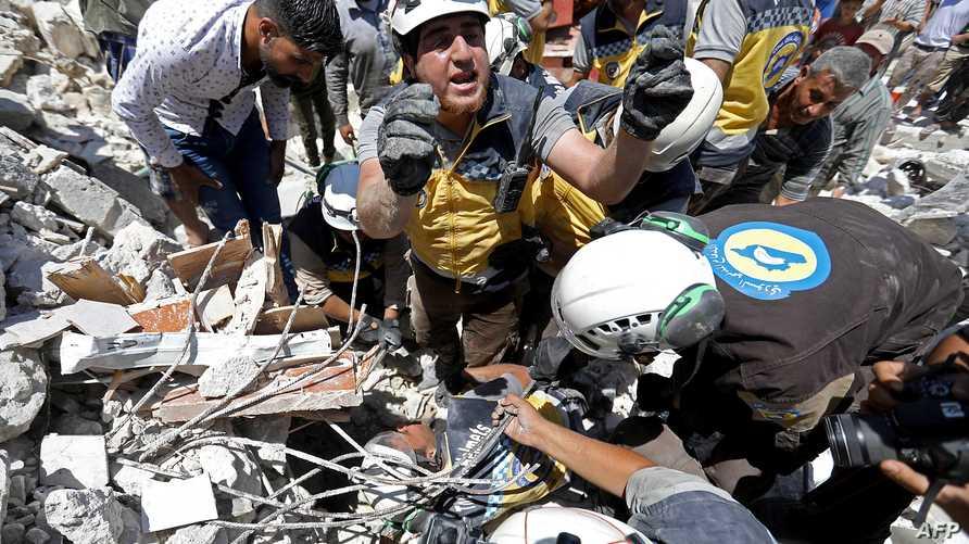 """مجموعات من """"الخوذ البيضاء"""" ينتشلون طفلا جريحا من تحت أنقاض الغارة على سوق في معرة النعمان بإدلب السورية في 22 يوليو"""