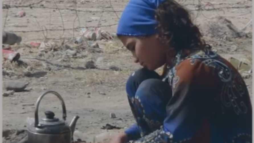 طفلة نازحة إلى مخيم عين عيسى تشعل النار تحت إبريق الشاي/إرفع صوتك