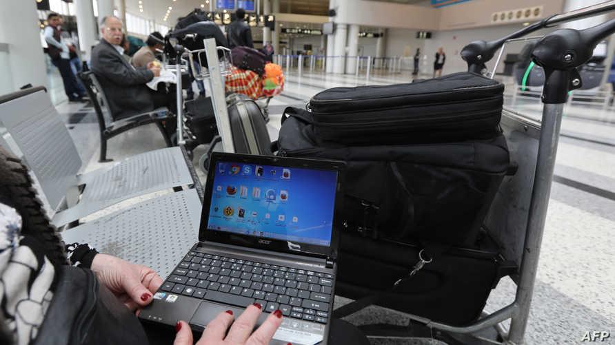 مسافرة إلى أميركا تستخدم حاسوبها في مطار عمان - أرشيف
