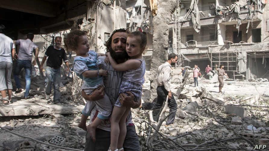 رجل يحمل طفلتيه في منطقة تعرضت للقصف في حلب- أرشيف
