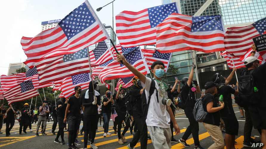 المتظاهرون في هونغ كونغ يرفعون العلم الأميركي خلال مسيرهم نحو القنصلية الأميركية في المدينة