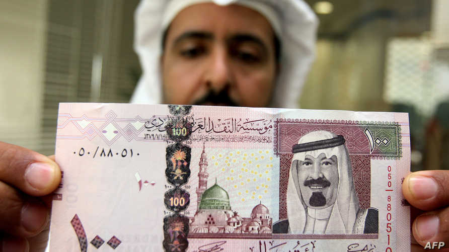 موظف في أحد البنوك السعودية يحمل ورقة نقدية من فئة 100 ريال