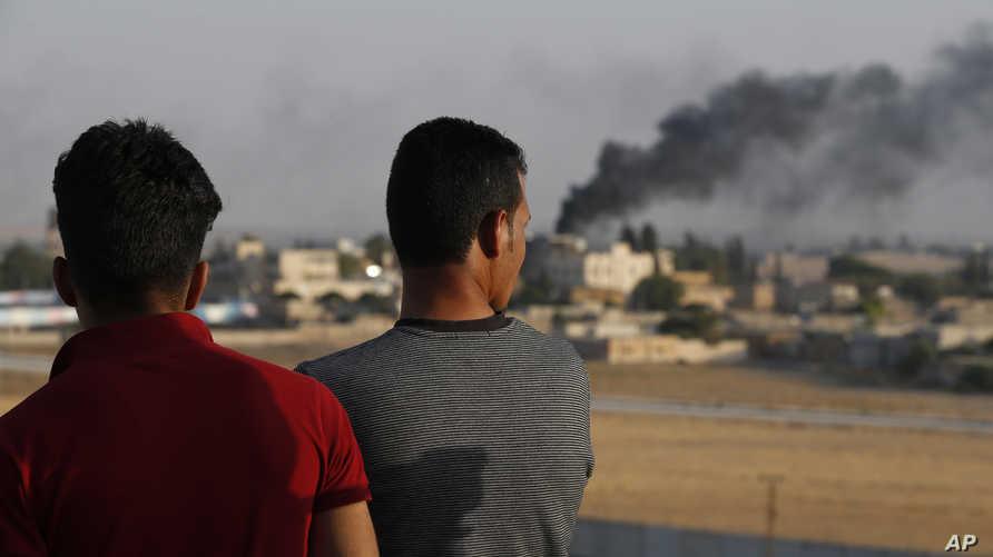 رجلان يتابعان من الجانب التركي عمليات قصف على تل الأبيض في سوريا في 13 أكتوير