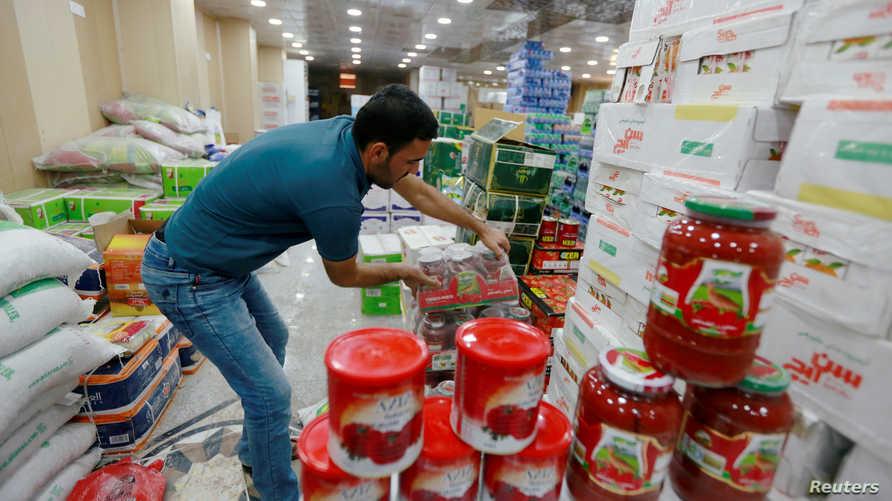 عامل في متجر يرتب علب معجون طماطم إيراني الصنع في سوبر ماركت في مدينة النجف