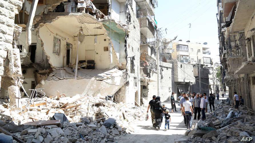 أشخاص يمشون بين ركام البنايات في منطقة تعرضت للقصف في حلب- أرشيف