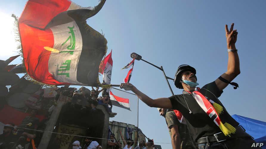 متظاهر يحمل علما عراقيا قرب جسر الجمهورية المؤدي للمنطقة الخضراء وسط بغداد