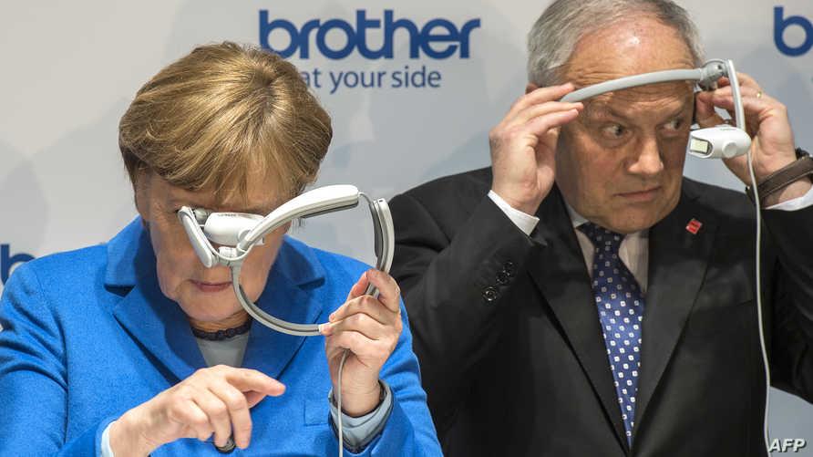 المستشارة الألمانية أنجيلا ميركل والرئيس السويسري السابق يوهان شنايدر أمان في مؤتمر تكنولوجي