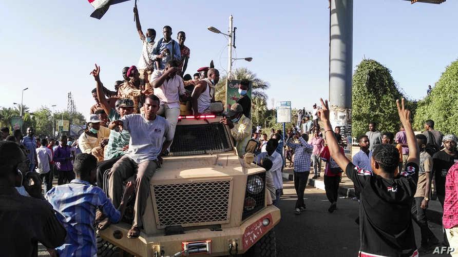 متظاهرون على متن عربة  عسكرية يلوحون بعلامات النصر وإعلام السودان