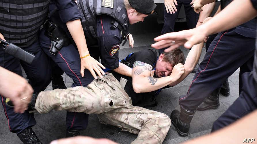 """رجال شرطة روس يعتقلون متظاهر خلال مظاهرة ضد """"حصانة"""" وكالات إنفاذ القانون في موسكو - يونيو 2019"""