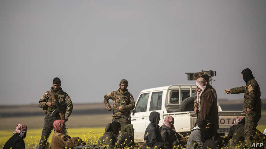 عناصر من قسد مع رجال غادروا الباغوز ويشتبه في انتمائهم لداعش