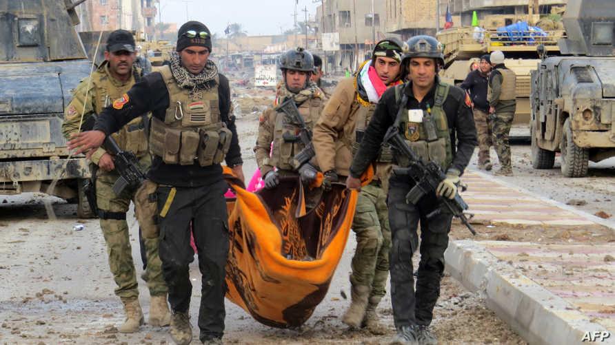 جنود عراقيون يحملون جثة زميل لهم خلال معارك تطهير الرمادي